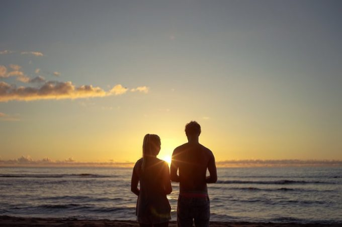 夕日を見る夫婦の写真