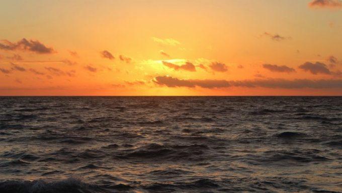 夕日の沈む水平ラインの写真